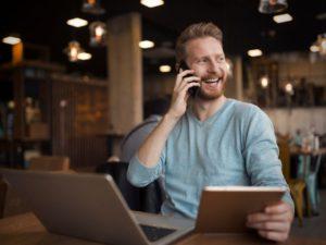 Man on the phone while sitting at his laptop, hiring a marketing freelancer