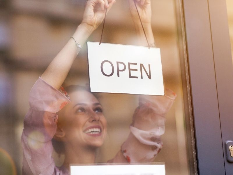 Photo of a woman hanging an open sign the a window of a small business